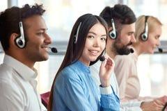 Корейская девушка в центре телефонного обслуживания с коллегами Стоковое Изображение RF