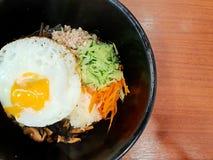 Корейский стиль еды, взгляд сверху риса покрыт с закалёнными овощами, мясом и стороной вверх по яичнице на верхней части в черном Стоковое Фото