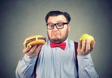 Коренастый человек делая выбор в диете стоковое изображение rf