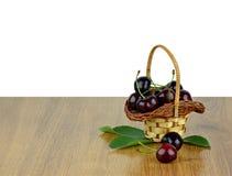 Корзина вишен с листьями на деревянной предпосылке / Изолят Стоковое Фото