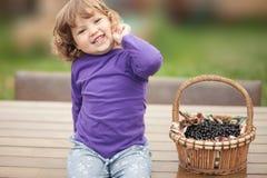 Корзина вполне ягоды черной смородины и счастливой девушки малыша Стоковые Фото