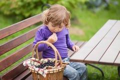 Корзина вполне ягоды черной смородины и счастливой девушки малыша Стоковые Фотографии RF
