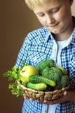 Корзина владением мальчика с зелеными овощами Стоковые Фото