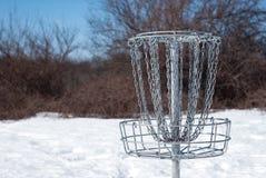 Корзина гольфа диска в снеге стоковые фотографии rf
