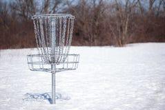 Корзина гольфа диска в снеге стоковое фото rf