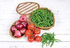 Корзина зеленых фасолей с томатами и луками Стоковая Фотография