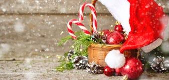 Корзина знамени рождества праздника сияющая с конусами шариков, игрушек, конфеты и сосны, шляпой Санта Клауса на винтажной деревя Стоковая Фотография RF
