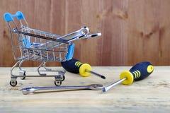 Корзина от супермаркета заполнила с ключами рядом отвертки стоковая фотография