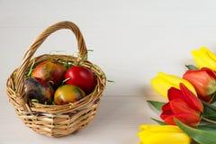 Корзина пасхи плетеная с покрашенными яичками и желтыми и красными тюльпанами на белой деревянной доске Стоковые Изображения