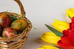 Корзина пасхи плетеная с покрашенными яичками и желтыми и красными тюльпанами на белой деревянной доске Стоковые Фото