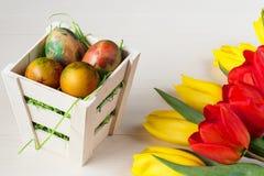 Корзина пасхи плетеная с покрашенными яичками и желтыми и красными тюльпанами на белой деревянной доске Стоковая Фотография