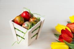 Корзина пасхи плетеная с покрашенными яичками и желтыми и красными тюльпанами на белой деревянной доске Стоковые Фотографии RF