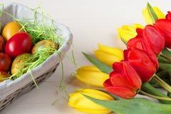Корзина пасхи плетеная с покрашенными яичками и желтыми и красными тюльпанами на белой деревянной доске Стоковая Фотография RF