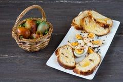 Корзина пасхи плетеная с покрашенными яичками и отрезанным хлебом пасхи в белой плите на серой деревянной доске Стоковое Изображение