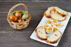 Корзина пасхи плетеная с покрашенными яичками и отрезанным хлебом пасхи в белой плите на серой деревянной доске Стоковая Фотография