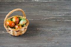 Корзина пасхи плетеная с покрашенными яичками на серой деревянной доске Стоковые Фотографии RF