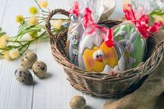 Корзина пасхи с пряником пасхи Яйца триперсток вокруг Мы подготавливаем на яркий праздник стоковое фото