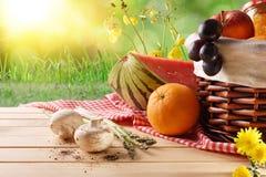 Корзина пикника плетеная с едой на таблице в крупном плане поля стоковая фотография rf