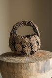 Корзина руки сделанная конусов сосны помещенных на журнале Стоковое Изображение