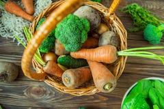 Корзина соломы взгляд сверху с овощами сада - свежими морковами, свеклами, брокколи, луками на деревенской деревянной предпосылке Стоковое Изображение