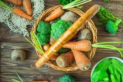 Корзина соломы взгляд сверху с овощами сада - свежими морковами, свеклами, брокколи, луками на деревенской деревянной предпосылке Стоковые Фото