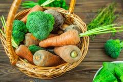Корзина соломы взгляд сверху с овощами сада - свежими морковами, свеклами, брокколи, луками на деревенской деревянной предпосылке Стоковые Фотографии RF