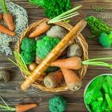 Корзина соломы взгляд сверху с овощами сада - свежими морковами, свеклами, брокколи, луками на деревенской деревянной предпосылке Стоковое Фото