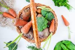 Корзина соломы с овощами сада - свежими морковами, свеклами, брокколи, луками на белой деревянной предпосылке Еда сбора фермы или Стоковое Фото