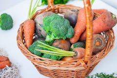 Корзина соломы с овощами сада - свежими морковами, свеклами, брокколи, луками на белой деревянной предпосылке Еда сбора фермы или Стоковое Изображение RF