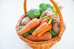 Корзина соломы с овощами сада - свежими морковами, свеклами, брокколи, луками на белой деревянной предпосылке Еда сбора фермы или Стоковое Изображение