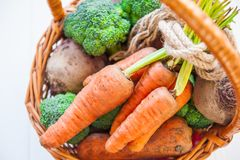 Корзина соломы с овощами сада - свежими морковами, свеклами, брокколи, луками на белой деревянной предпосылке Еда сбора фермы или Стоковое фото RF