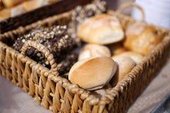 Корзина сплетенная лозой свежего испеченного хлеба на рынке ` s фермера Стоковое Изображение RF