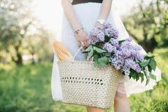 Корзина с букетом сиреней и багета в руках женщины на предпосылке природы стоковые изображения