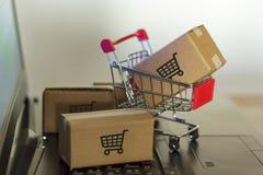 Корзина с коробкой на компьютере Онлайн покупки, электронная коммерция и всемирная грузя концепция стоковое фото rf