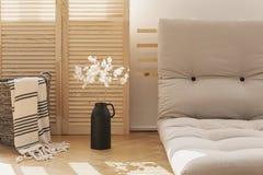 Корзина с одеялом и белыми цветками в естественном интерьере живущей комнаты Реальное фото стоковые изображения