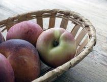 Корзина с персиками на таблице Стоковое Изображение