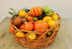 Корзина с свежими томатами на деревянном столе Стоковые Изображения