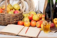 Корзина яблок, бутылки сидра и старая тетрадь Стоковые Фотографии RF