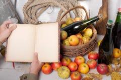 Корзина яблок, бутылки сидра и старая тетрадь Стоковое Изображение