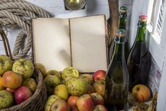 Корзина яблок, бутылки сидра и старая тетрадь Стоковое Фото