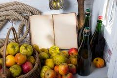 Корзина яблок, бутылки сидра и старая тетрадь Стоковая Фотография RF