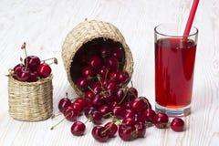 Корзины и сок вишни на деревянной предпосылке Стоковая Фотография