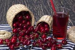Корзины и сок вишни на деревянной предпосылке Стоковые Изображения