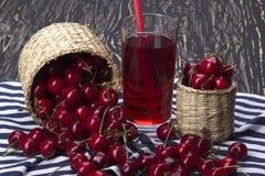 Корзины и сок вишни на деревянной предпосылке Стоковое Изображение