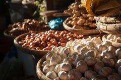 Корзины с чесноком и луками на рынке Стоковое Фото