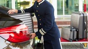 Коридорный принимая багаж гостя от автомобиля thee к его комнате стоковые изображения rf