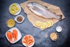 Коричневая бумага ремесла с сырыми рыбами, кусками лимона креветки семг на белой плите, лимоном, перцем и солью помещена на темно стоковое изображение rf