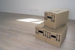 коричневая коробка карточки пакета в пустой белой комнате с окнами и деревянным настилом, окнах и двери в предпосылке - Moving дн Стоковое Изображение RF
