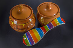 2 коричневых глиняного горшка с покрашенной керамической ложкой на черной предпосылке Стоковые Фотографии RF