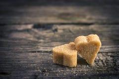 2 коричневых сердца тростникового сахара на старом деревянном столе Стоковые Изображения